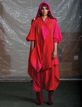 Model standing up wearing a bright red and pink outfit with beaded veil and dark red velvet heeled boots.