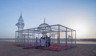 Architecturally recognisable mosque form made out of chicken wire and metal poles with chandelier, carpeting in red and with worshippers inside. Set outside in a sandy landscape with a backdrop of blue sky.