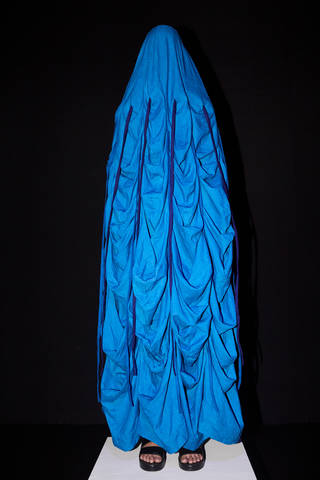 Model wearing a bright blue ruched shroud covering her entire head and body, except her feet