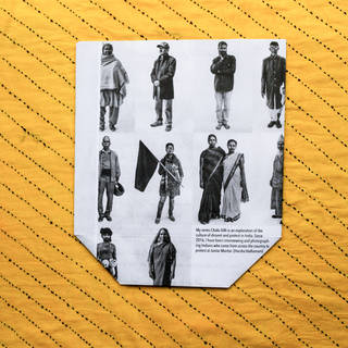 Bright yellow striped square of packaging material with a central photo of standing men and women in Indian dress