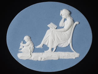 Flat oval plaque of white Jasperware with blue dip and applied white bas-relief decoration. A woman sits cross-legged on a chair in left profile, reading a book. She wears a mob-cap and holds her right hand up to her face. A child on the floor before her plays with a doll.