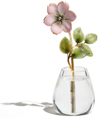 Pink enamel rose with green leaves standing in a clear rock crystal vase