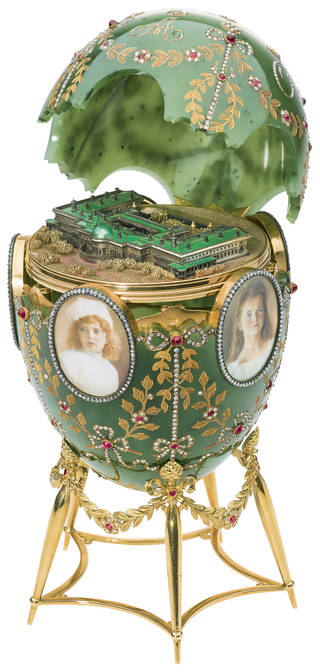 Green Faberge easter egg on stand with open lid showing a model of the Alexander Palace inside
