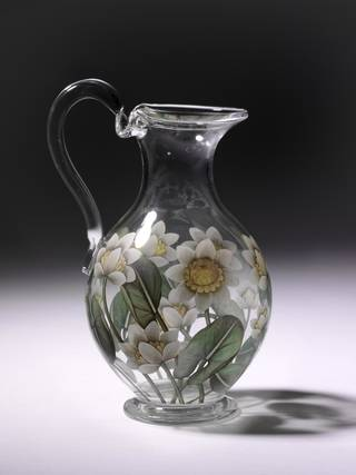 Transparent glass water jug decorated with white flowers which have a yellow centre and green stems and leaves
