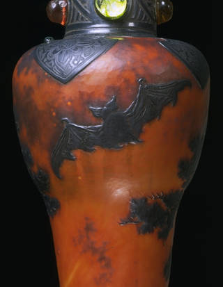 Orange and black vase decorated with raised glass, black bats, and forest imagery