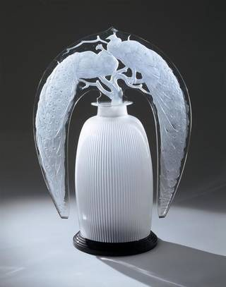 Glass lamp, the 'stopper' press moulded and decorated with two perching peacocks. The main body of the lamp is ribbed