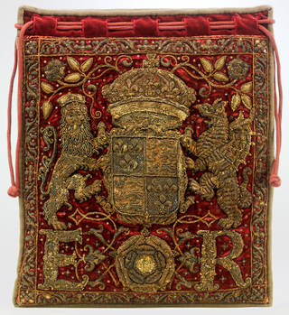 Drawstring deep red velvet bag richly embroidered in gold and featuring a lion, dragon and the initials E.R.
