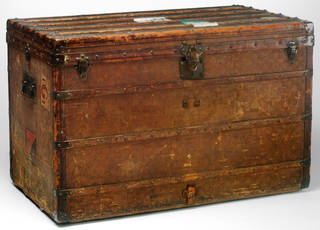 Large , rectangular brown travelling trunk with flat top, bands around it, handles at the sides and a lock at the front.