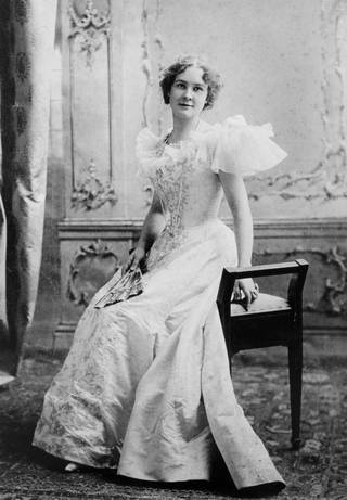 Black and white photograph of a woman in a long white evening gown perched on a stool.