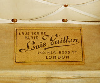Louis Vuitton label detail from the inside of a travelling trunk in cream and tan colours