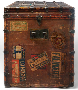 End view of a brown travel trunk covered in stickers from ocean liner travel.
