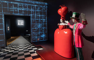 Interior view of Alice: Curiouser and Curiouser showing Queen of Hearts and Mad Hatter costumes