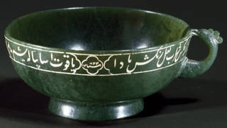 Dark green jade cup with handle, inscribed with white Persian writing around the top edge.