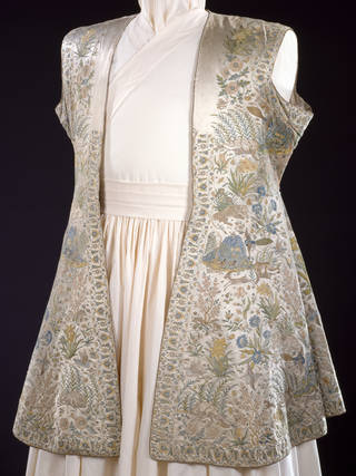 Heavily embroidered sleeveless coat featuring birds, animals, flowers and plants on an ivory background and mounted on a mannequin.