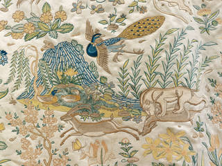 Detail of fine embroidery of deer, lions, ducks, peacocks and butterflies in blues, greens, yellows on ivory background