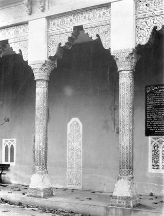 Black and white photograph of part of the highly decorated and inlaid colonnade at Agra showing floral designs.