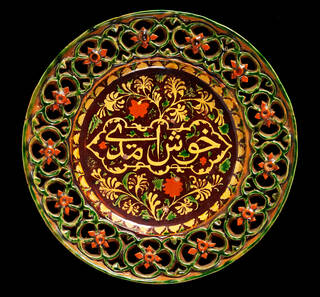 A circular dish with an openwork rim, made of glazed earthenware. 'Welcome' is written in underglaze slip in Persian/Urdu. The dish is glazed in green, brown and orange.