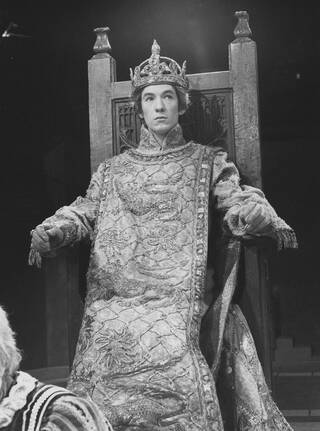 Black and white photograph of Ian McKellen in Richard II costume, sat on a wooden throne. He wears a jewelled crown, and a long tabard with patterned detailing depicting lions