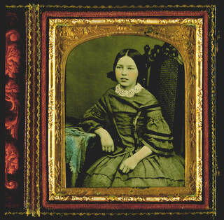 Hand-coloured photograph in greens and blues of a young girl sat in a mesh backed chair with arm resting on table. In gold, red and black rectangular frame.