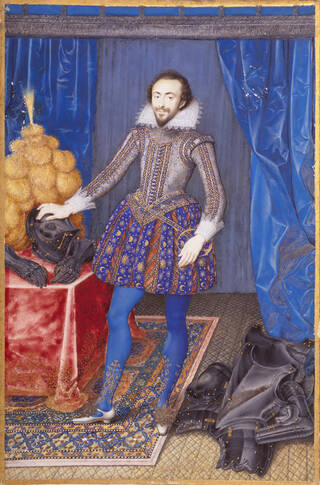 Man standing up in a room with background of blue curtain and wall. Wearing elaborate, decorative outfit with puffed blue breeches, blue tights and silver shoes. There is a suit of armour on the floor and table.
