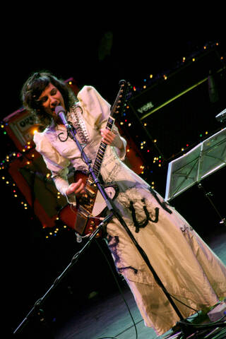 PJ Harvey wearing the white dress with leg-of-mutton sleeves and blue embroidered detailing, whilst performing. She sings into a microphone and holds a red guitar.