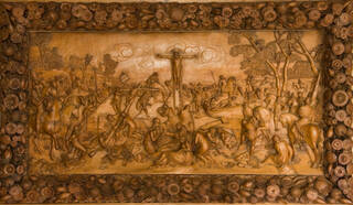 Mid-brown carved wooden panel with floral border depicting a crucifixion.