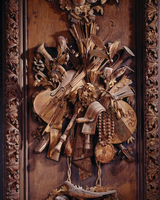 Detail of a decorative carved wooden panel depicting musical instruments, flowers and foliage.