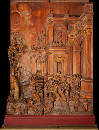Detailed wooden carved panel in browns and orange tones with a crowd scene and the architural facades of buildings