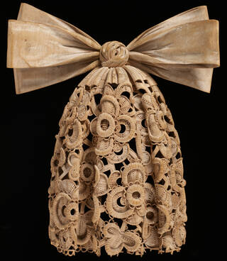 Intricately detailed lace cravat carved in lime wood with a large bow.