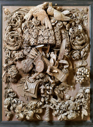 Highly detailed carved wooden panel featuring flora and fauna, two doves, fruit, sword hilts and crowns.