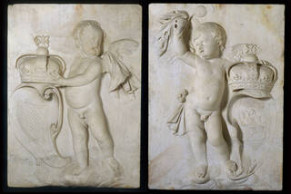 Pair of pale stone carvings of Putti holding crowns, one standing next to a harp and the other holding a thistle.