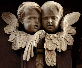 Wooden carving of two Putti heads surrounded by flowers on a dark wooden background