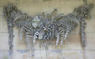 Grey unfired clay floral swag attached to a pale, bare block wall.