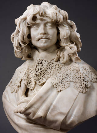 Pale marble bust of a man with curly shoulder-length hair and an elaborate lace collar.