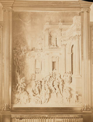 Sepia toned photograph of the carved wooden panel depicting the Stoning of St Stephen hung on a wall in a frame.