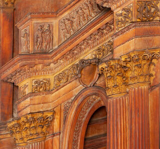 Section of detail from a carved wooden panel depicting the Stoning of St Stephen, orange and yellow tones of wood