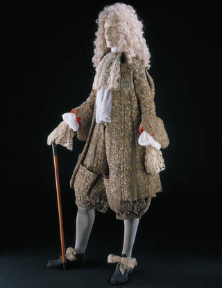 Mannequin wearing a very fine suit of breeches and long coat with lace cravat and cuffs, carrying a cane and wearing lace up shoes.