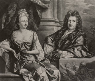 Black and white portrait of a man and woman seated and wearing expensive looking clothes with a backdrop of pillars and swagged curtains.