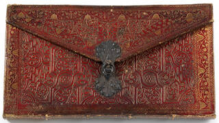 Red leather envelope style pocket sketch book with metal clasp. Leather has been tooled in an intricate pattern.