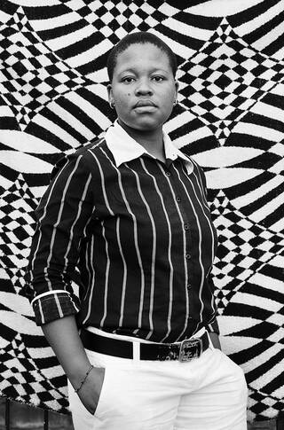 Portrait of a woman wearing black-and-white clothing against a black-and-white patterned textile background.