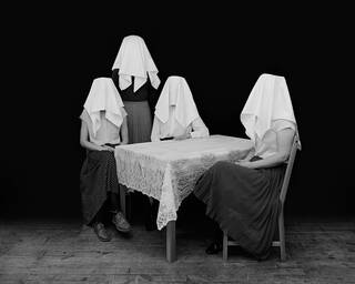 Three figures sit around a dining table, one stands behind. All have white cloths over their heads hiding their faces.