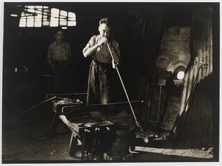 A man glass-blowing in a darkened industrial setting