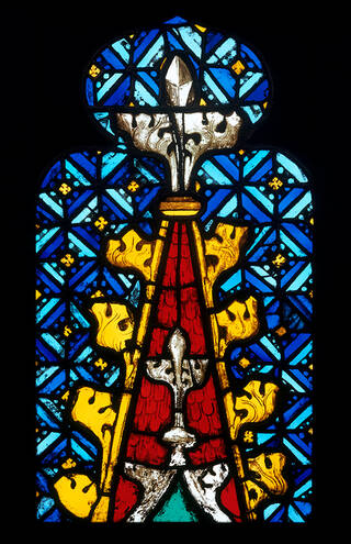 An elaborately designed panel depicting the top of a canopy in red, blue and yellow stained glass.