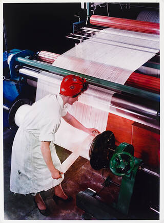 Woman in white overalls and a red headscarf working at huge rollers spinning yarn in a factory