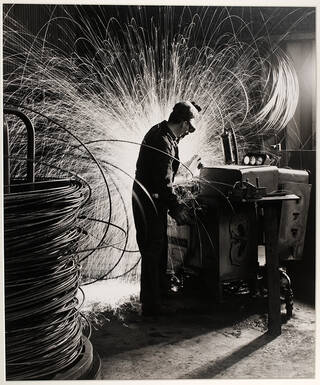 Factory worker surrounded by sparks and coils of wire