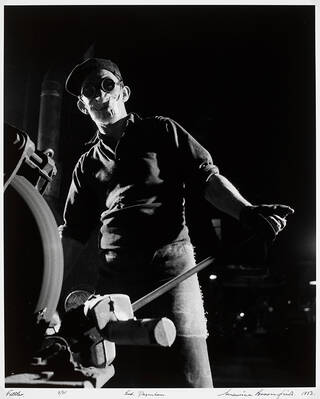 Heavily silhouetted figure wearing a face-mask and googles while operating machinery