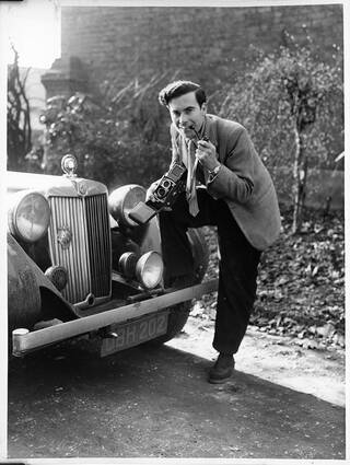 Portrait of Maurice smoking a pipe and smiling at the camera, leaning against his MG car