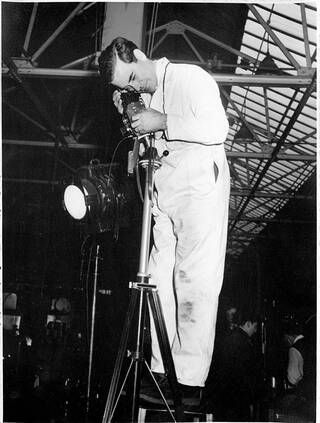 Maurice Broomfield photographing at a factory.