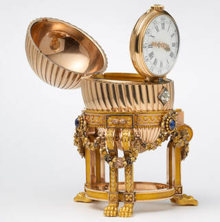 gold egg on a gold stand with clock inside, shown open