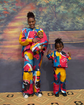 Colourful textile designs by Bethany Williams modelled by baby, child and woman against painted backdrop.